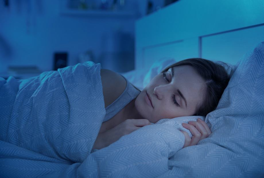 a lady sleeping in blue LED light