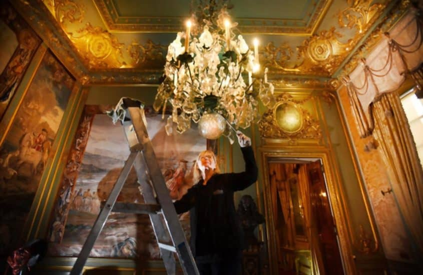 woman cleaning a chandelier