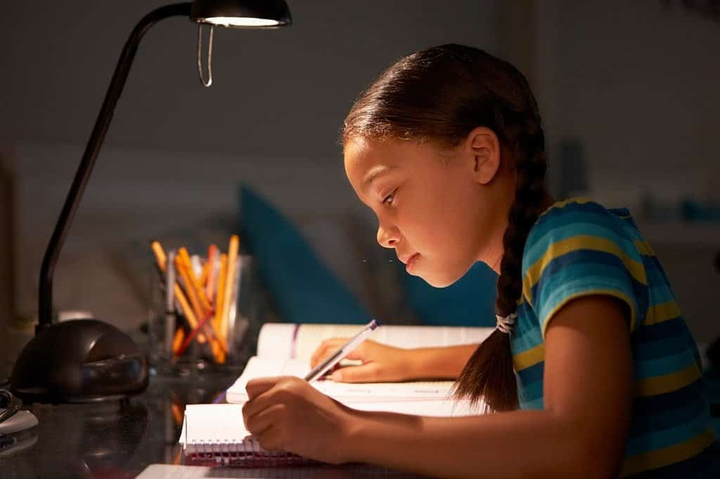 girl reading with a lamp