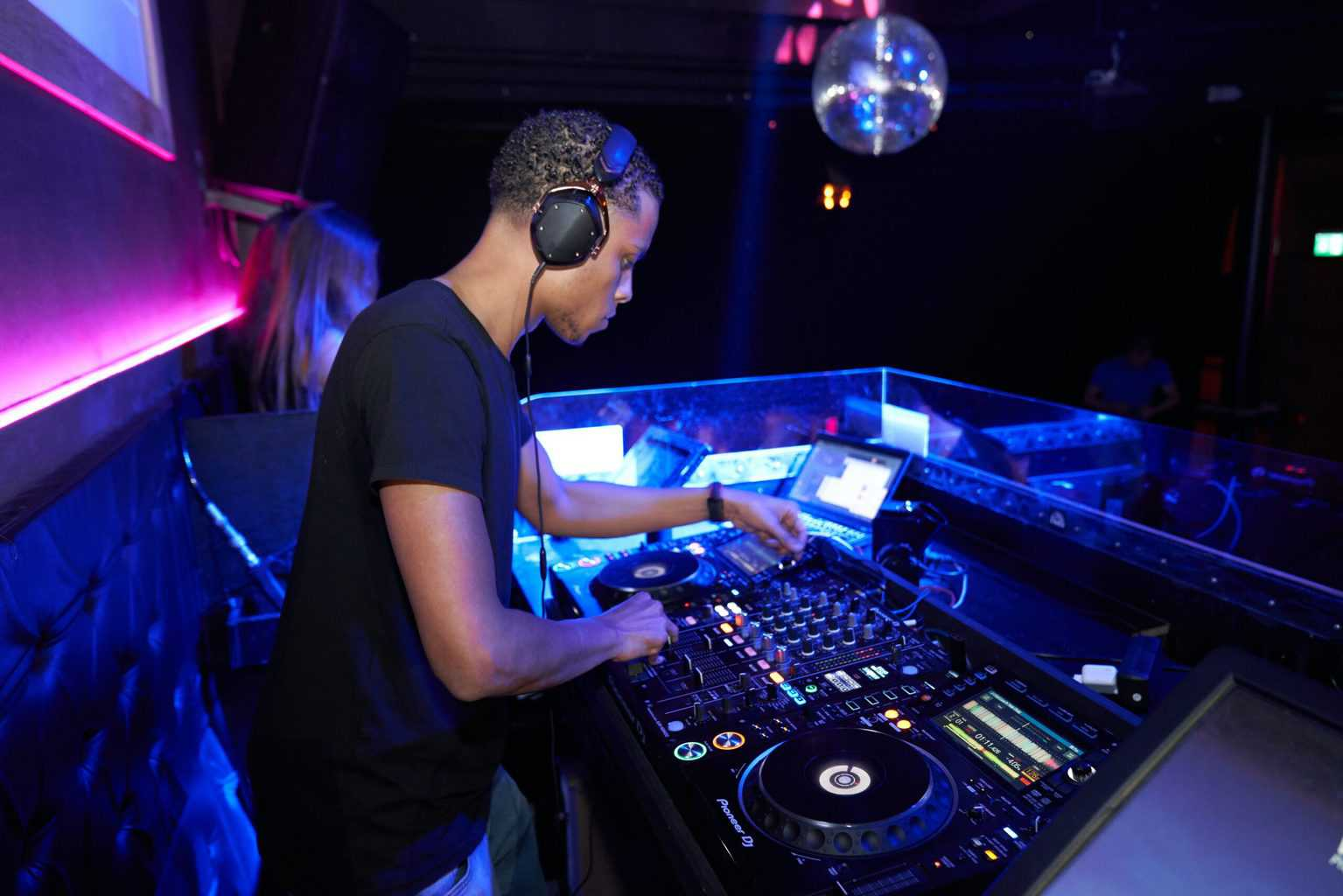 DJ mixing sounds at a party, while he's illuminated by lights