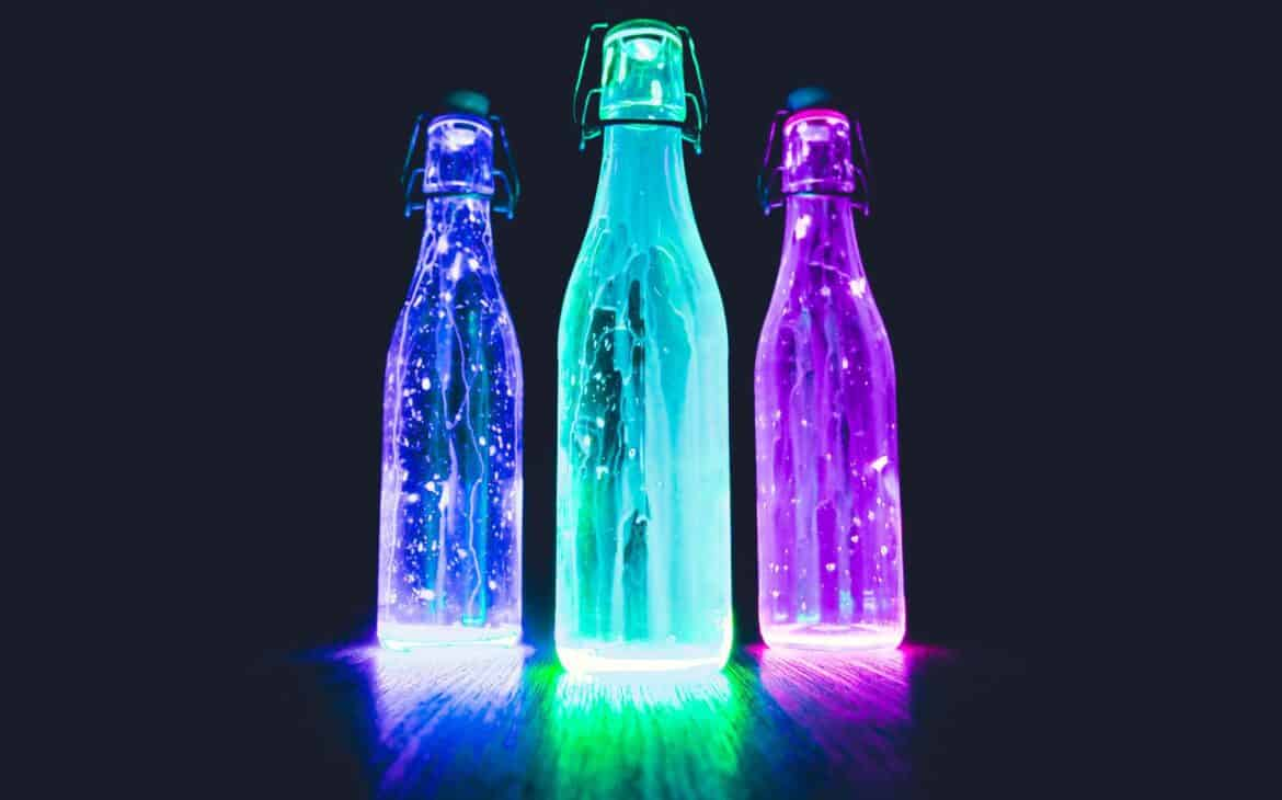 Lighted bottles, example of glow in the dark party ideas for adults