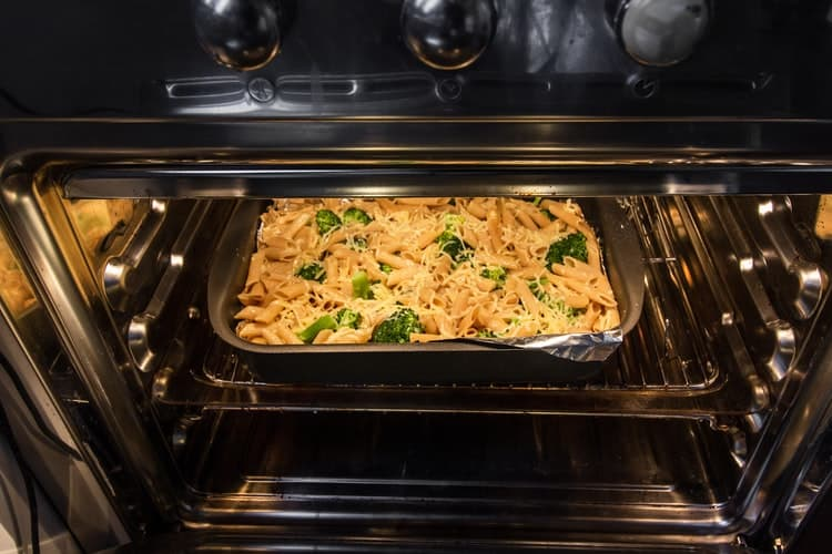 Opened oven with pasta dish about to be baked