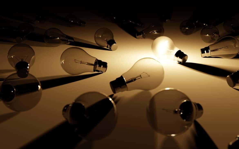 Unlit light bulbs encircling a lighted LED light bulb