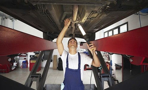 Man repairing car while holding a retractable work light
